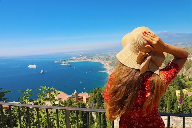 Vrouw die met hoed van mening van etna-vulkaan geniet van overweldigend dorp taormina in sicilië, italië