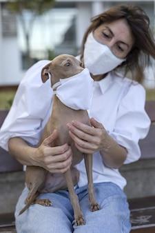 Vrouw die met hond speelt, die een coronavirus beschermend masker draagt