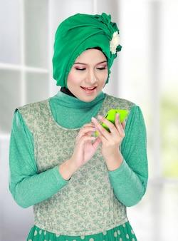Vrouw die met hoofdsjaal mobiele telefoon houdt
