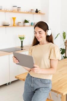 Vrouw die met hoofdtelefoons een tablet bekijkt