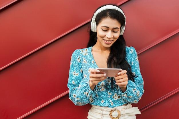 Vrouw die met hoofdtelefoons haar telefoon bekijkt
