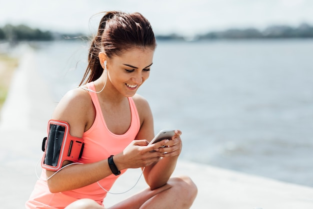 Vrouw die met hoofdtelefoons haar telefoon controleert