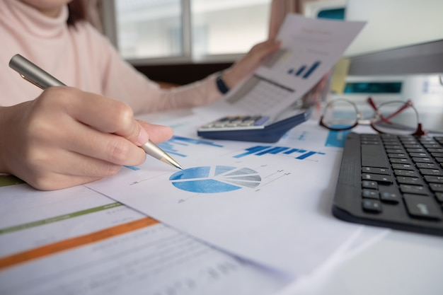 Vrouw die met jaarlijks financieel rapportsaldo werkt