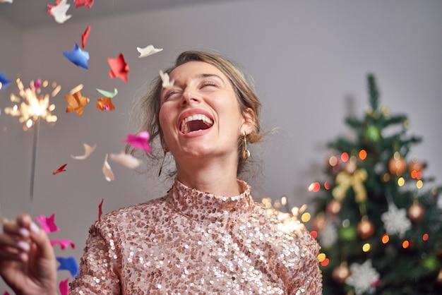 Vrouw die met kerstboom en sterretjes glimlacht