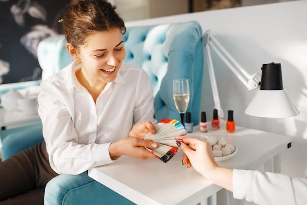 Vrouw die met kleurenpalet nagellak in schoonheidssalon, manicure en pedicureprocedure kiest.
