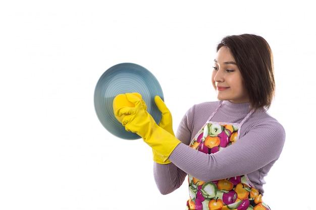 Vrouw die met kleurrijke schort een schotel wast