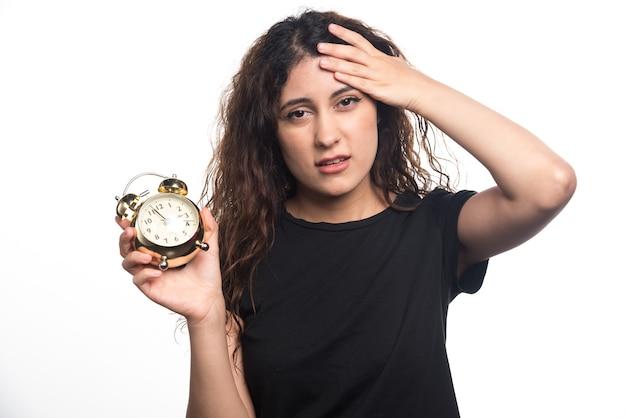 Vrouw die met klok haar hoofd op witte achtergrond houdt. hoge kwaliteit foto
