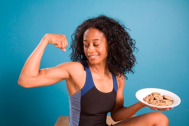 Vrouw die met koekjes buigt