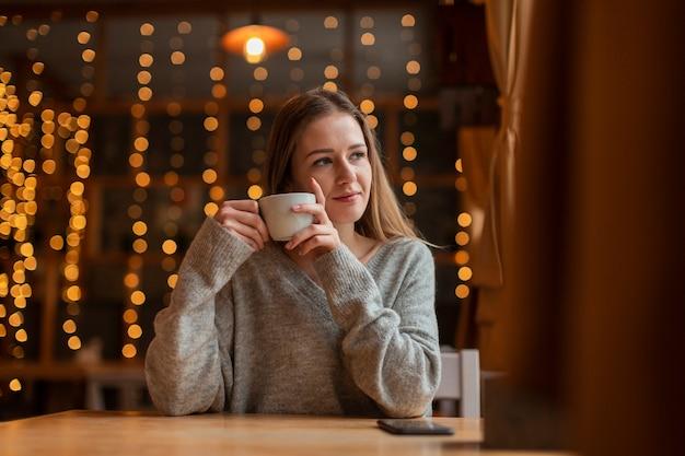 Vrouw die met koffie op venster kijkt