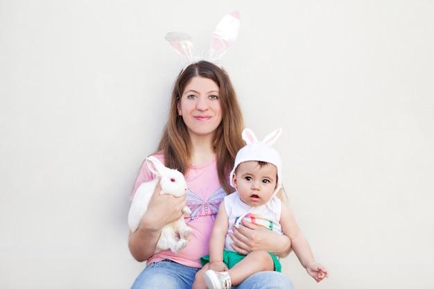 Vrouw die met konijntjesoren baby en een konijn houdt