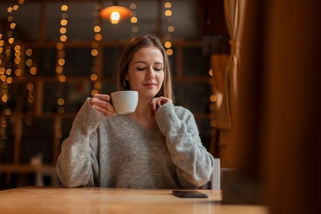 Vrouw die met kop van koffie mobiel bekijkt