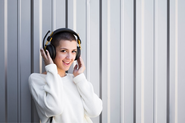 Vrouw die met kort haar aan muziek in hoofdtelefoons luistert en camera bekijkt