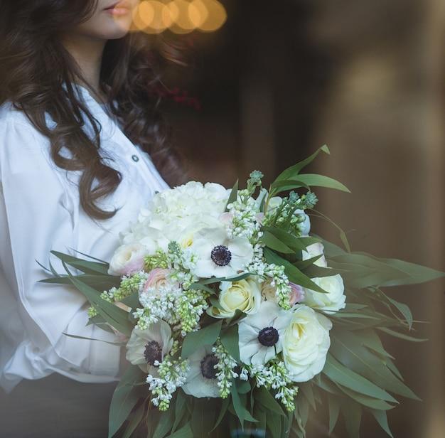 Vrouw die met krullende haren een wit boeket van bloemen houdt.