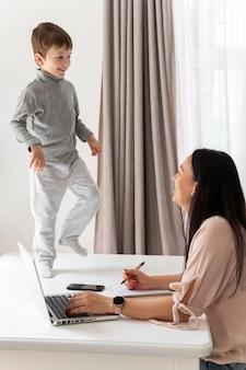 Vrouw die met laptop bij bureau werkt