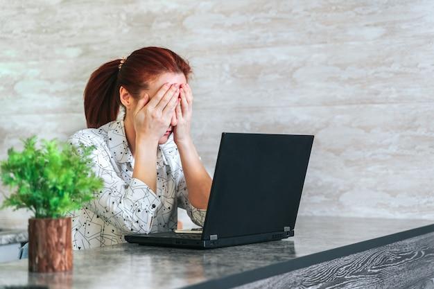 Vrouw die met laptop werkt die droevig, gefrustreerd bedekkend gezicht met handen voelt