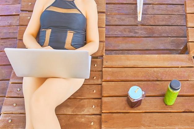 Vrouw die met laptop werkt die op houten terras voor mooie overzees ligt