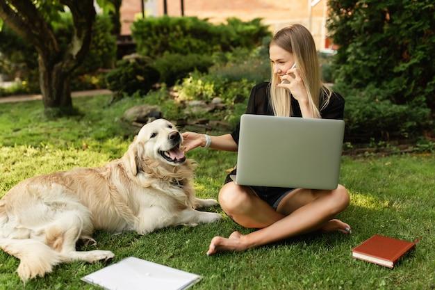 Vrouw die met laptop werkt en met hond labrador in park speelt