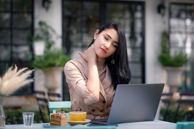 Vrouw die met laptopcomputer in tuin werkt en nekpijn heeft