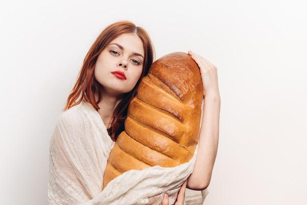 Vrouw die met lichte make-up een groot brood in haar handen koestert.