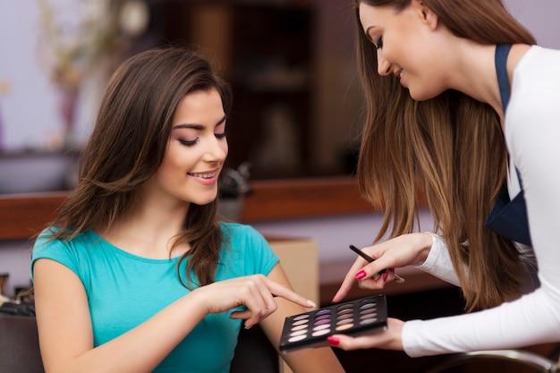 Vrouw die met make-upartiest kleur van oogschaduw kiest