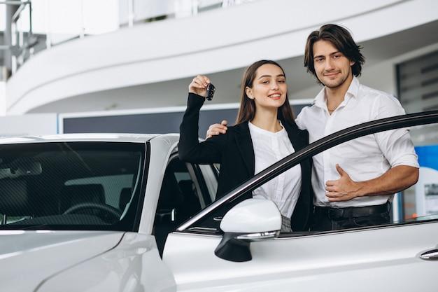 Vrouw die met mannelijke seles persoon in een autotoonzaal spreekt