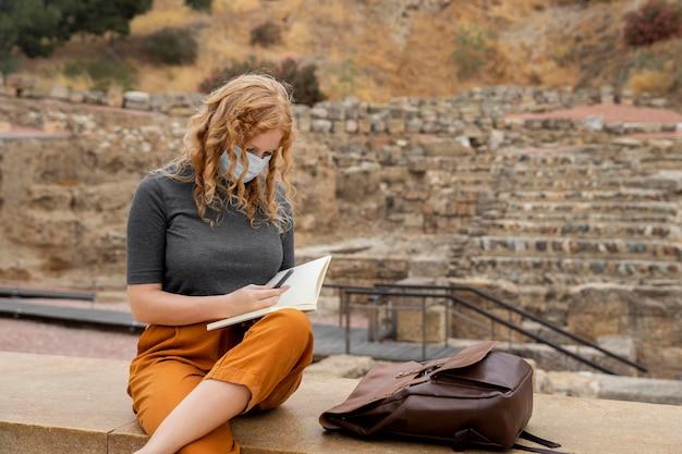 Vrouw die met masker in dagboek schrijft