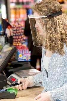 Vrouw die met masker voor boodschappen betaalt