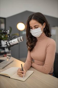 Vrouw die met medisch masker aan radio-uitzending voorbereidingen treft