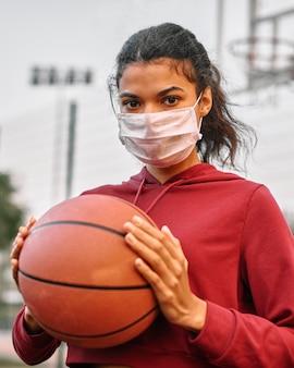 Vrouw die met medisch masker een basketbal houdt
