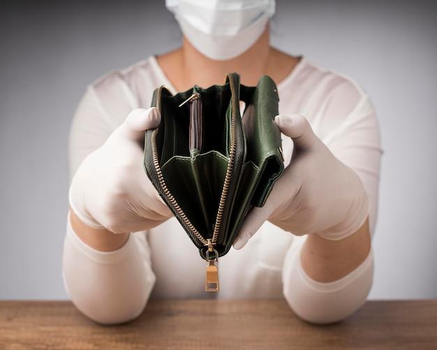 Vrouw die met medisch masker een lege portefeuille houdt
