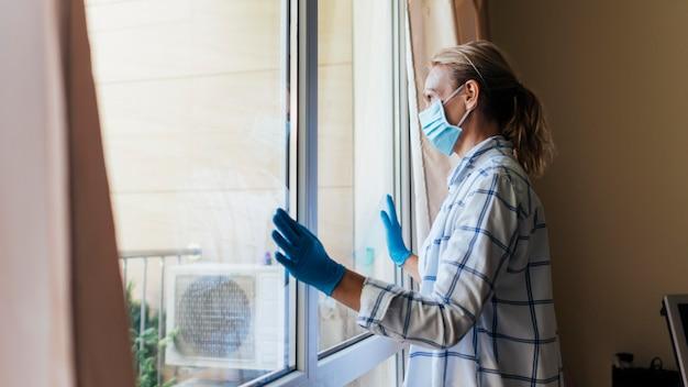 Vrouw die met medisch masker en handschoenen thuis door venster kijkt