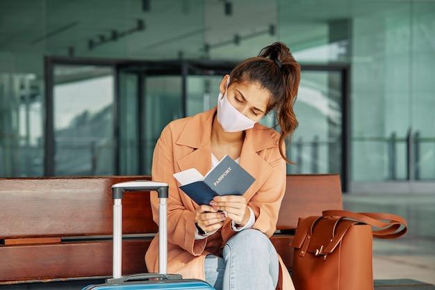Vrouw die met medisch masker haar paspoort controleert op de luchthaven tijdens pandemie