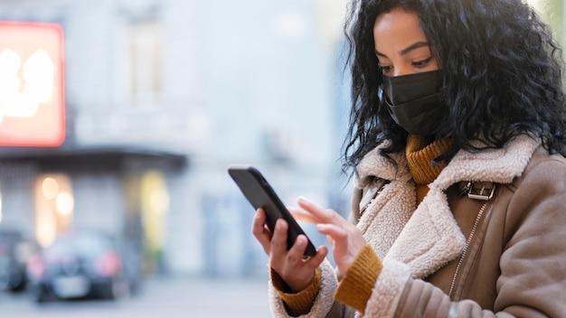 Vrouw die met medisch masker haar telefoon controleert