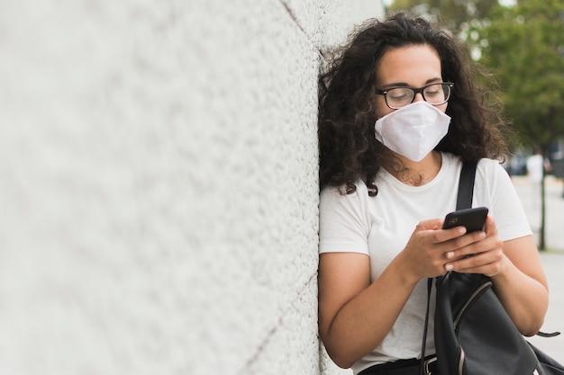 Vrouw die met medisch masker haar telefoon met exemplaarruimte controleert