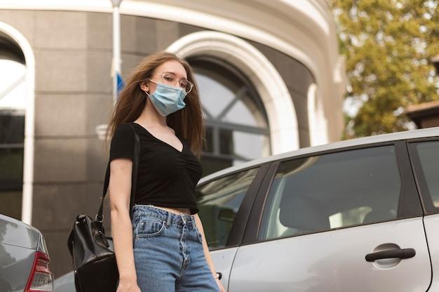 Vrouw die met medisch masker in de stad loopt