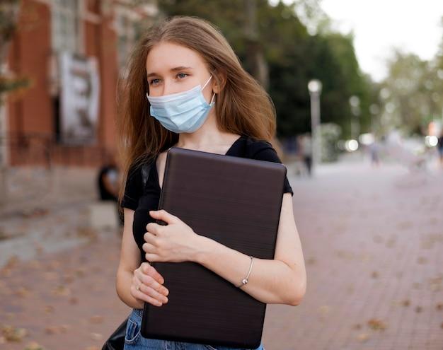 Vrouw die met medisch masker laptop houdt