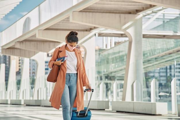 Vrouw die met medisch masker met haar bagage op de luchthaven loopt tijdens pandemie
