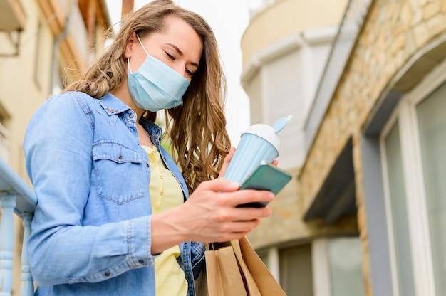 Vrouw die met medisch masker mobiele telefoon doorbladert