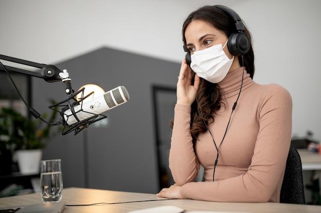 Vrouw die met medisch masker op radio uitzendt