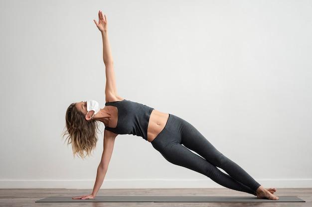 Vrouw die met medisch masker thuis yoga doet
