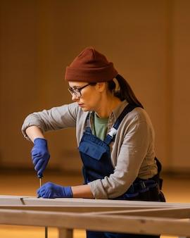 Vrouw die met middelgrote schot van de schroevedraaier werkt