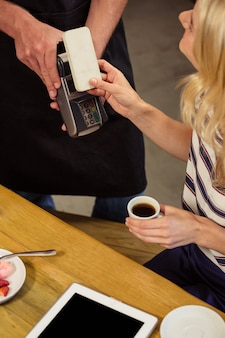 Vrouw die met mobiele betaling betaalt