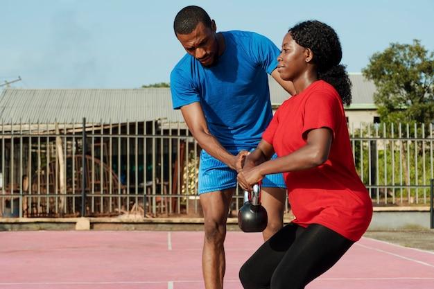 Vrouw die met persoonlijke trainer werkt