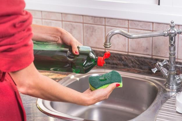 Vrouw die met rode manicure detergens in het schuursponsje zet