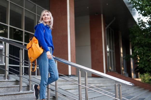 Vrouw die met rugzak de trappen van de universiteit afloopt