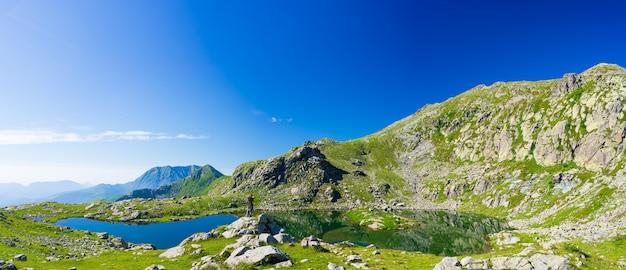 Vrouw die met rugzak op berg wandelt. een persoon op zoek naar uitzicht schilderachtige meer alpine landschap zomervakantie