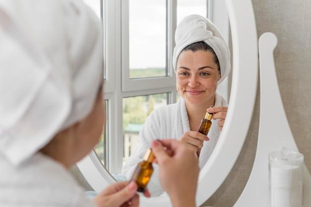 Vrouw die met serum in de spiegel kijkt