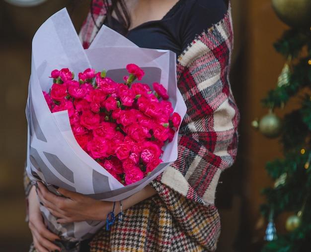Vrouw die met sjaal in de schouders een roze boeket van anjers houdt