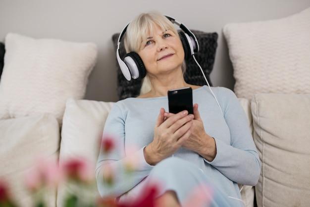 Vrouw die met smartphone aan muziek luistert