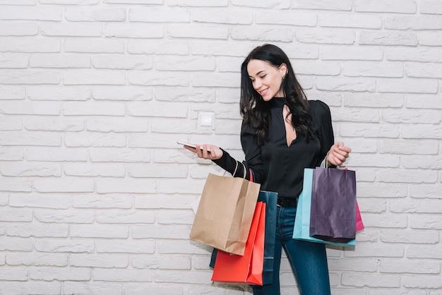 Vrouw die met smartphone kleurrijke zakken houdt